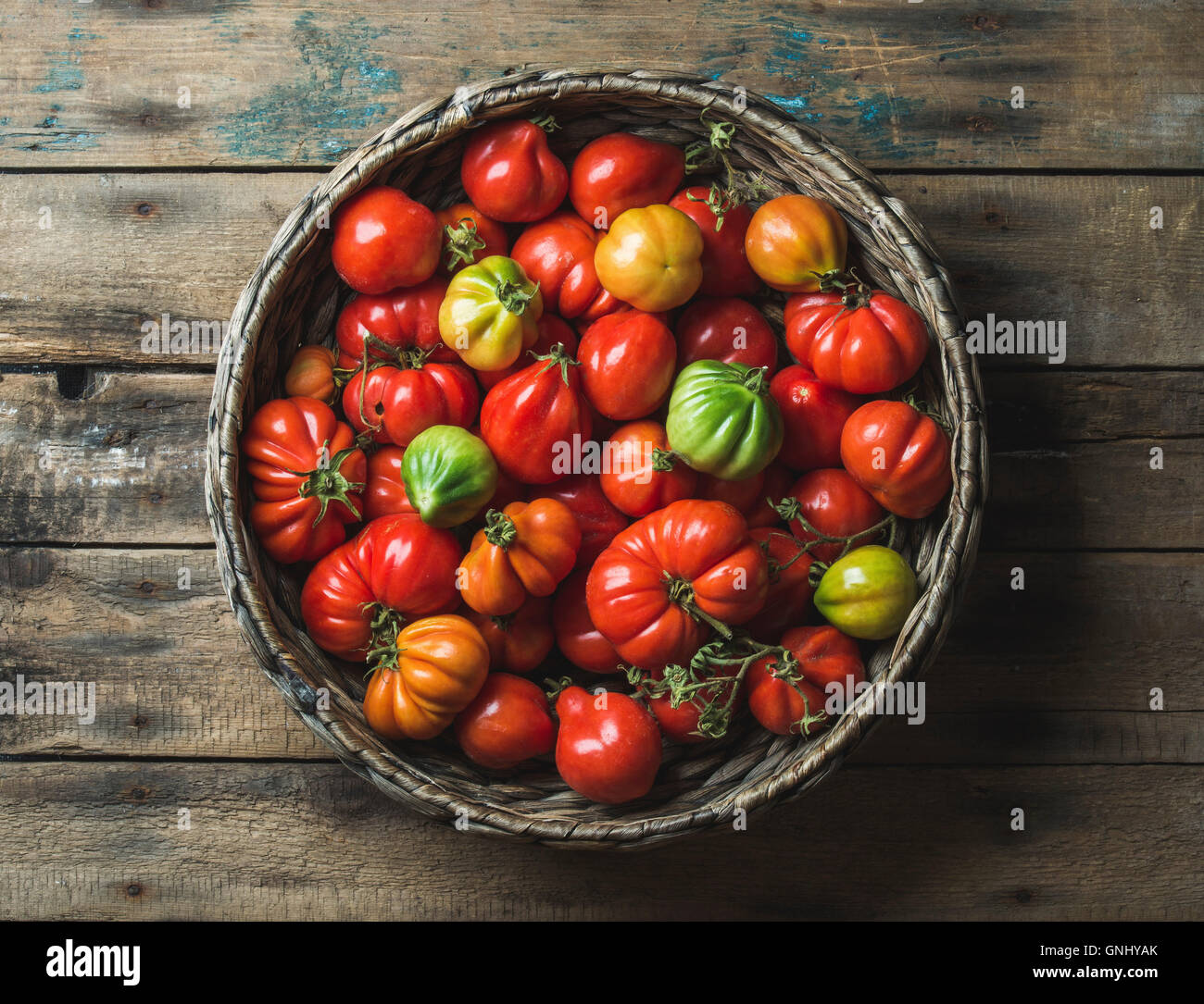 Fresh colorful ripe Fall heirloom tomatoes in basket over wooden background, top view, horizontal composition - Stock Image