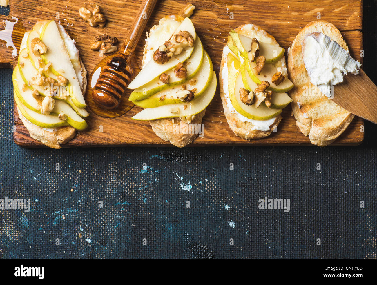 Crostini with pear, ricotta cheese, honey and walnuts. Breakfast toasts or snack sandwiches on rustic wooden board - Stock Image