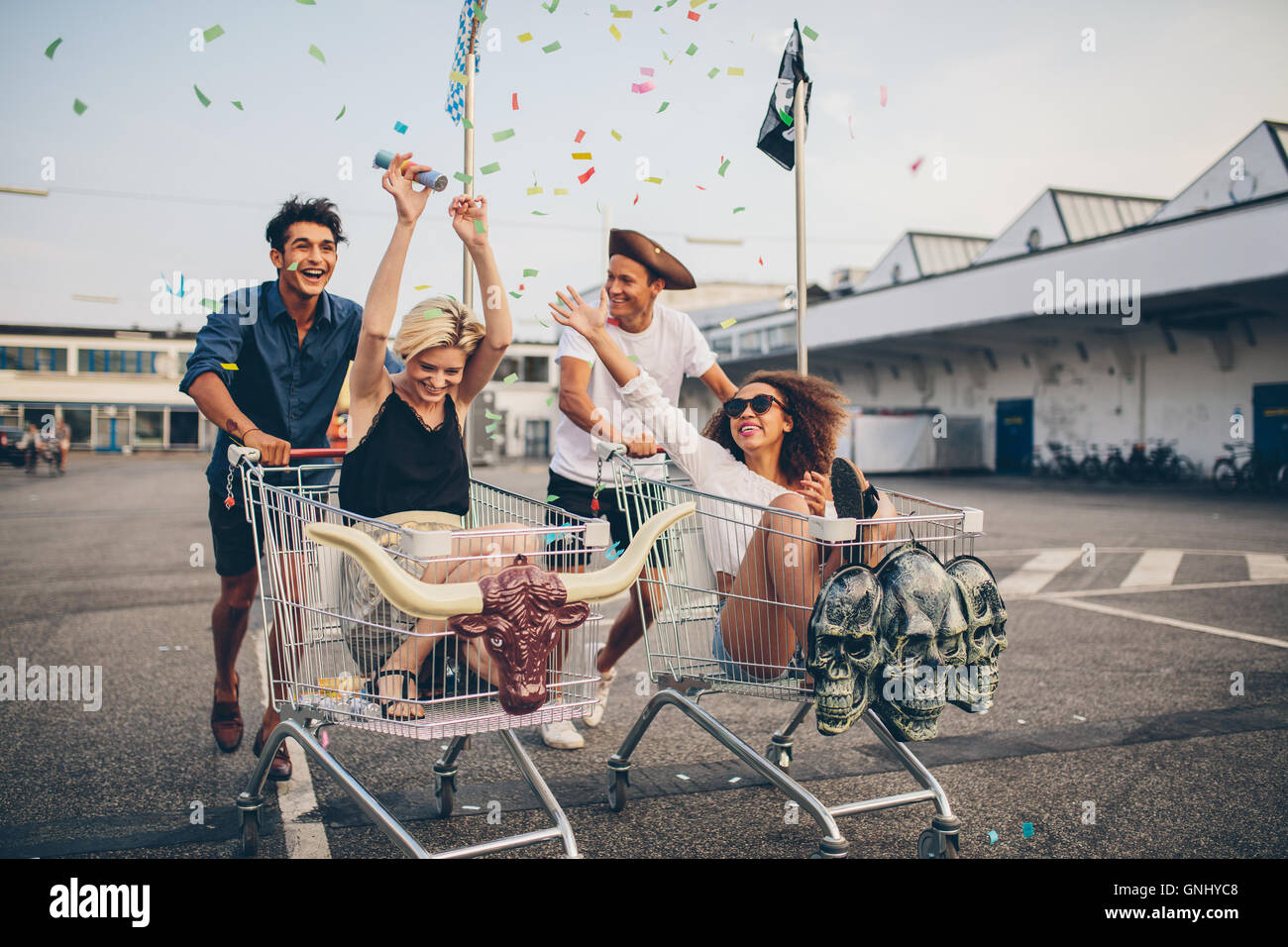 Young friends having fun on shopping trolleys. Multiethnic young people racing on shopping cart. - Stock Image