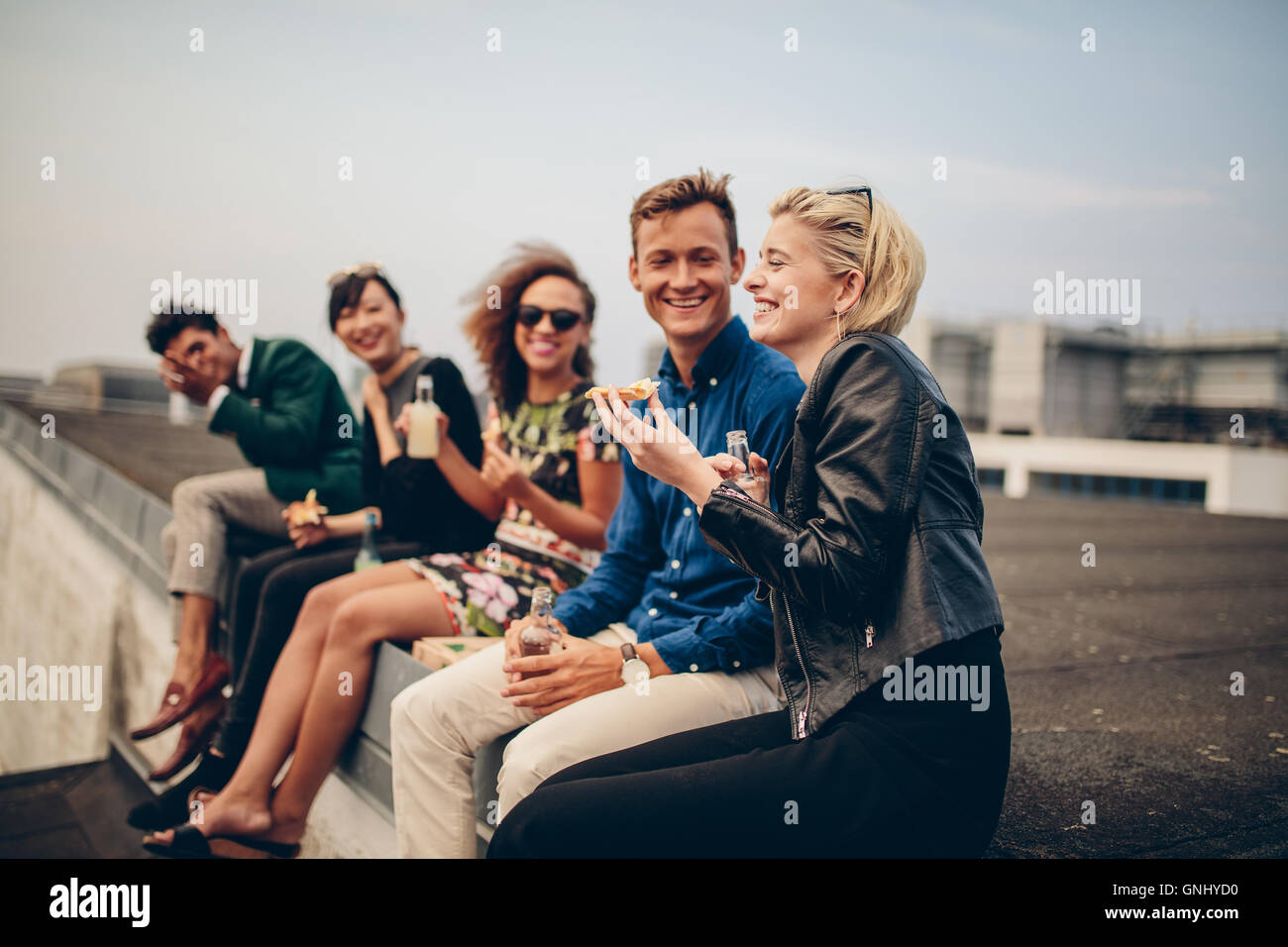 Shot of young people partying on terrace. Multiracial friends sitting together on rooftop having drinks and eating. - Stock Image