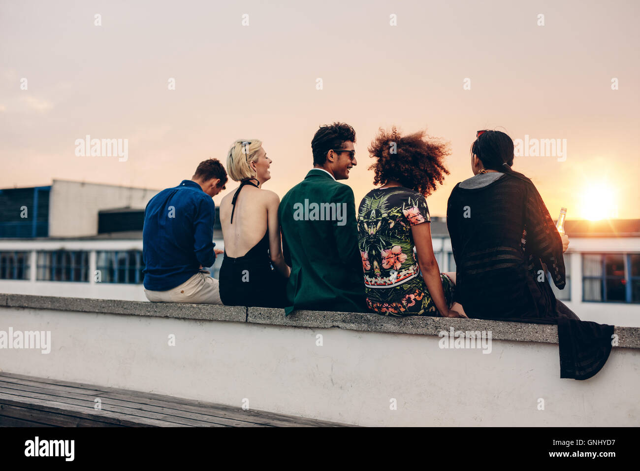 Rear view shot of young men and women sitting together on rooftop. Mixed race friends relaxing on terrace during Stock Photo