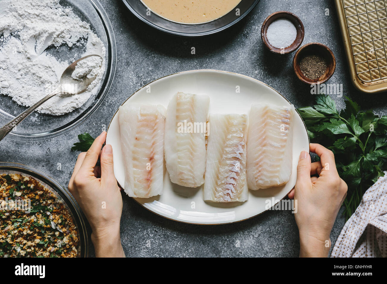 A woman is placing four cod fillets on the table. - Stock Image