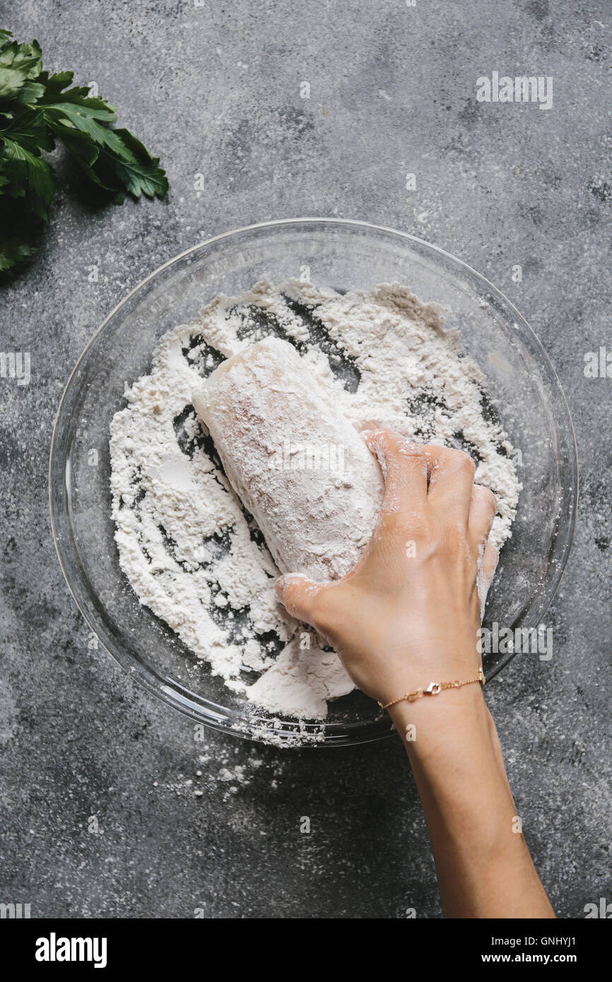 Step 1/4 A woman is coating a fish fillet with flour. Stock Photo