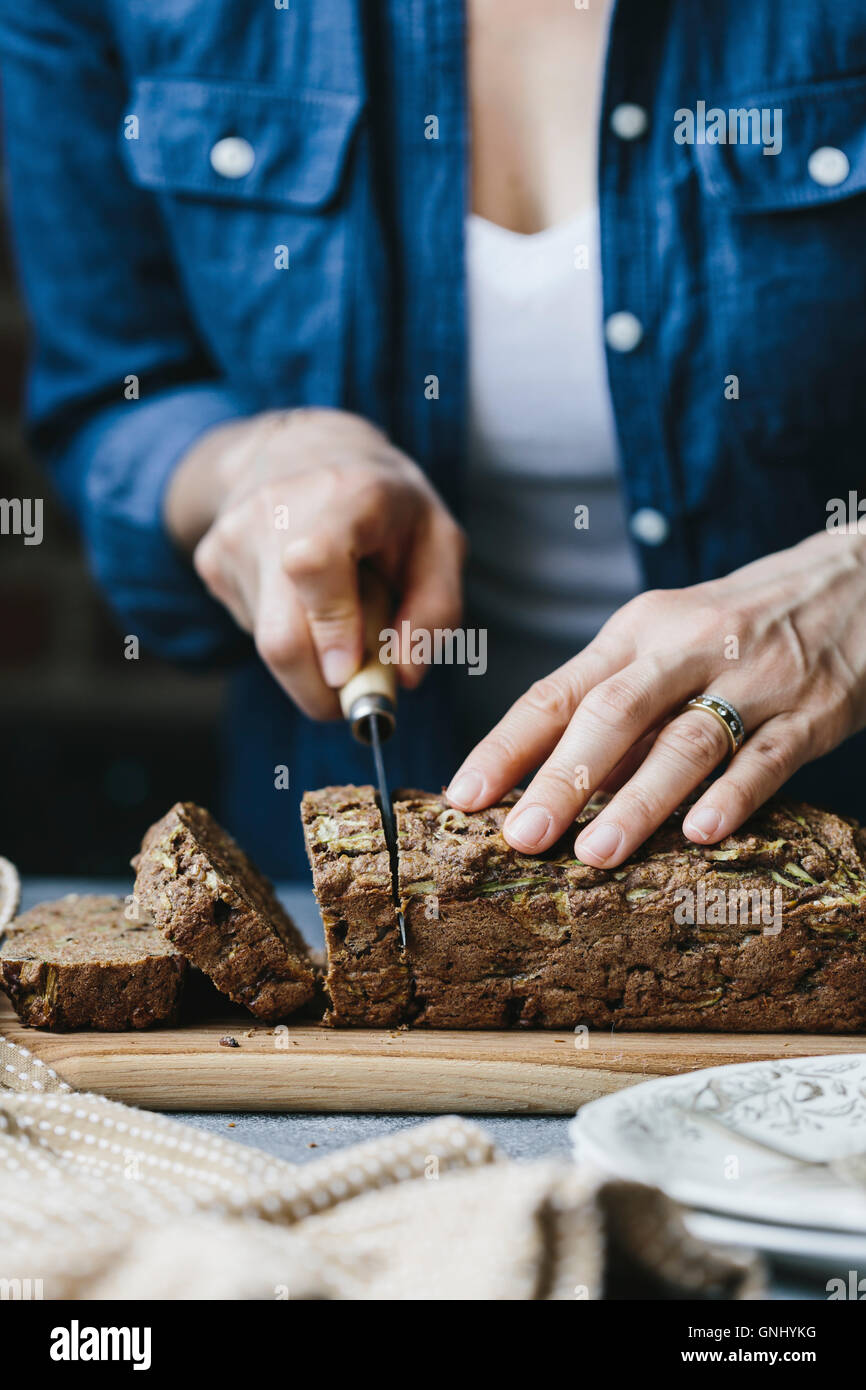 A woman is slicing a loaf of vegan zucchini and walnut bread. - Stock Image
