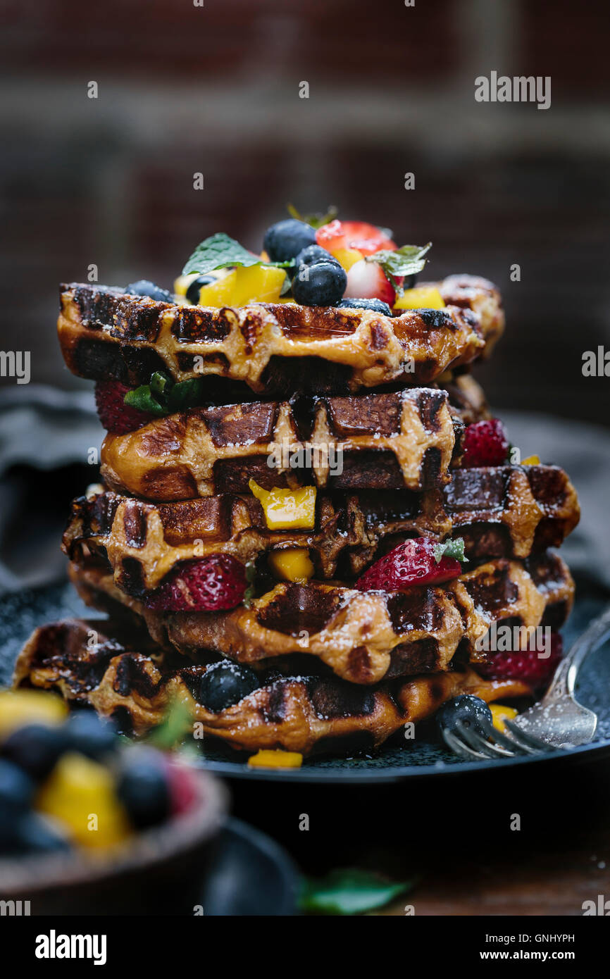Several brioche waffles are stacked and layered with fresh fruits and drizzled with maple syrup photographed from - Stock Image