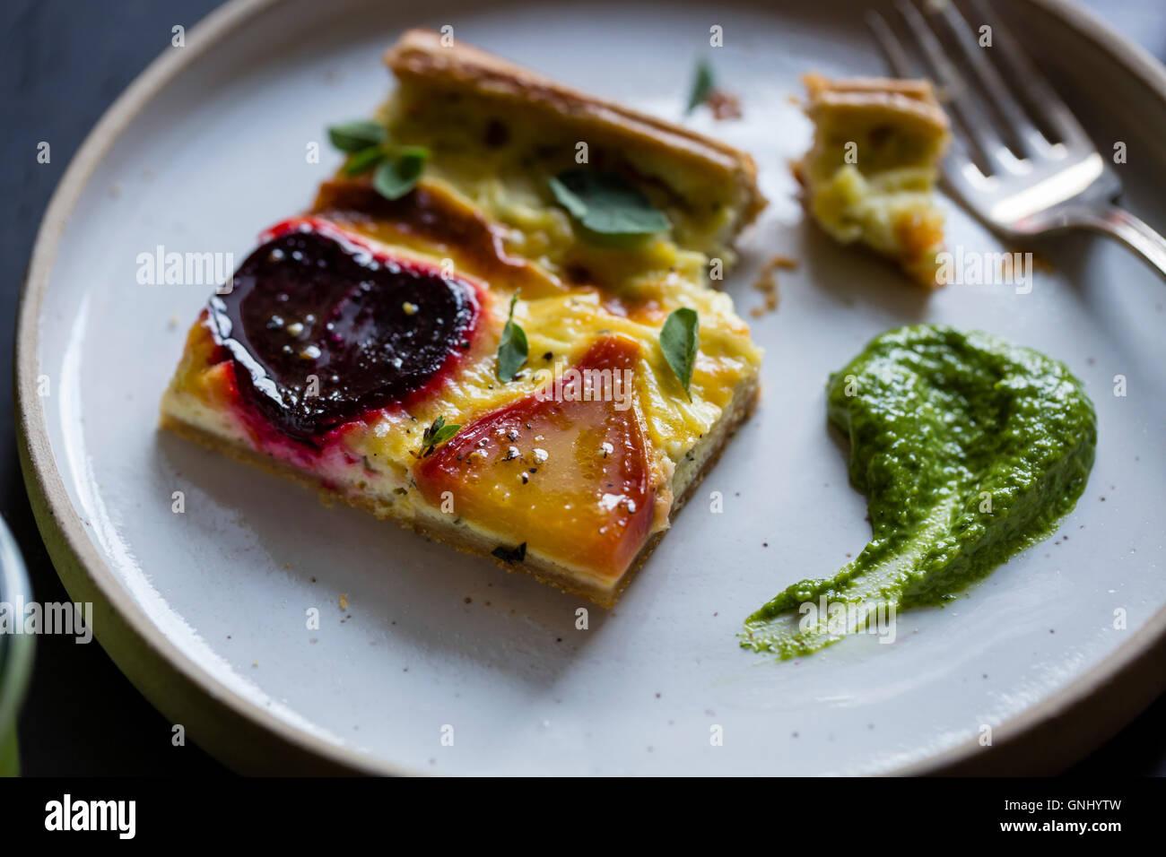 Beetroot ricotta cheese tart with beet greens pesto. Stock Photo