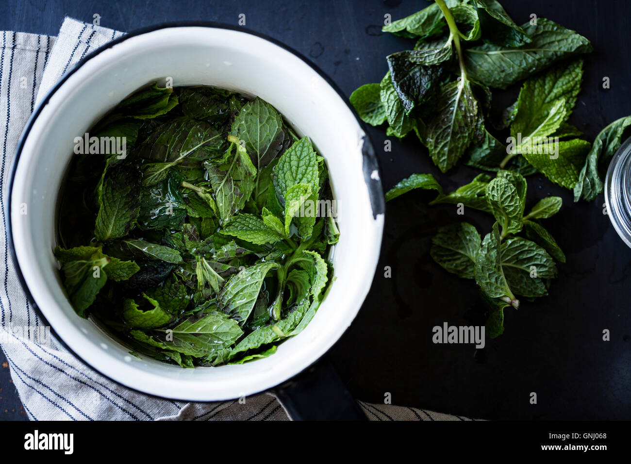 fresh mint leaves in a bowl - Stock Image