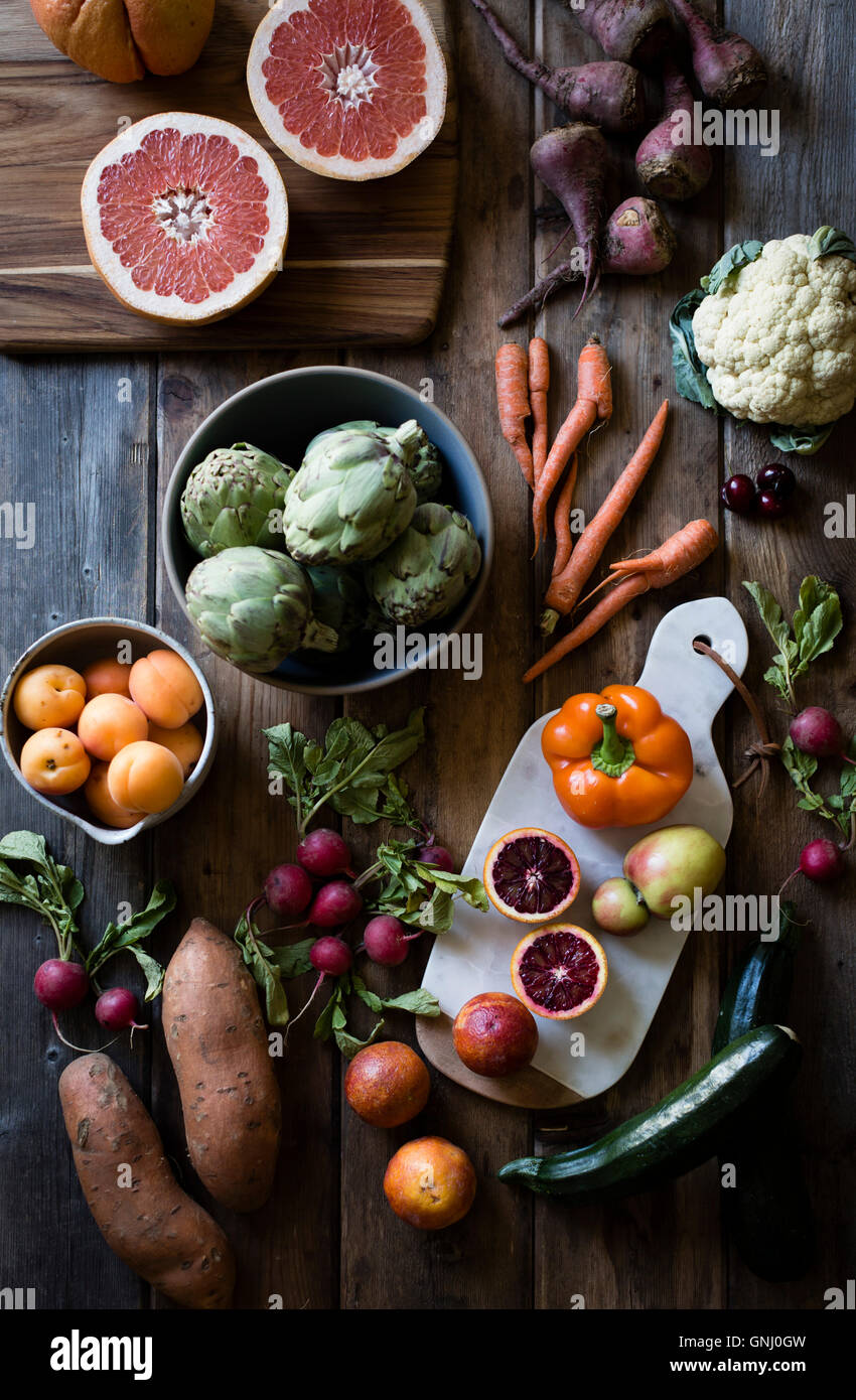 Fruit and vegetables laid out on a farm table. Carrots, cauliflowers, beets, peaches, oranges. Stock Photo