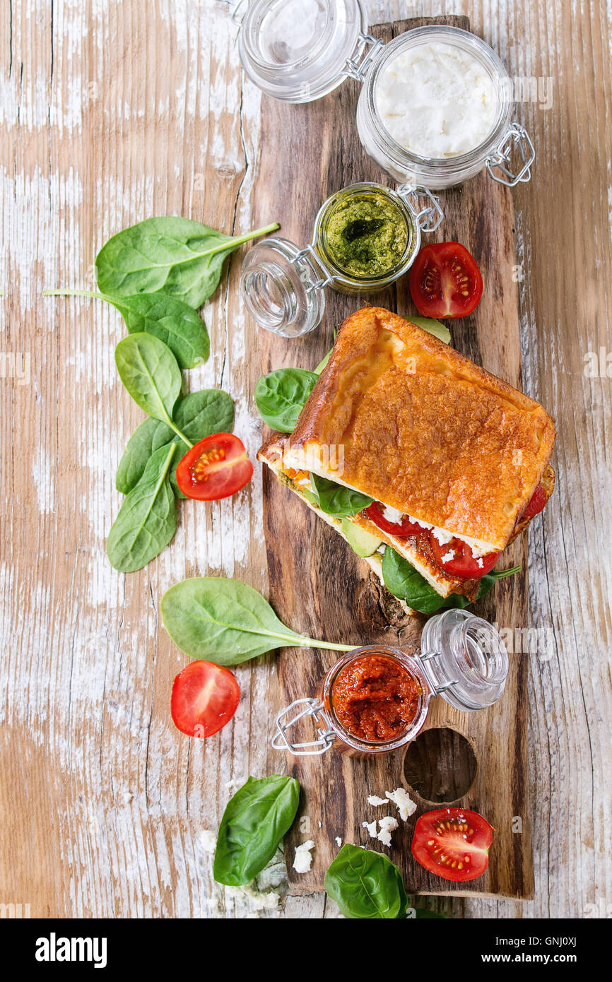 Low-carb gluten free Cloud bread veggie sandwich with spinach, avocado, feta cheese, tomatoes and pesto sauce, served - Stock Image