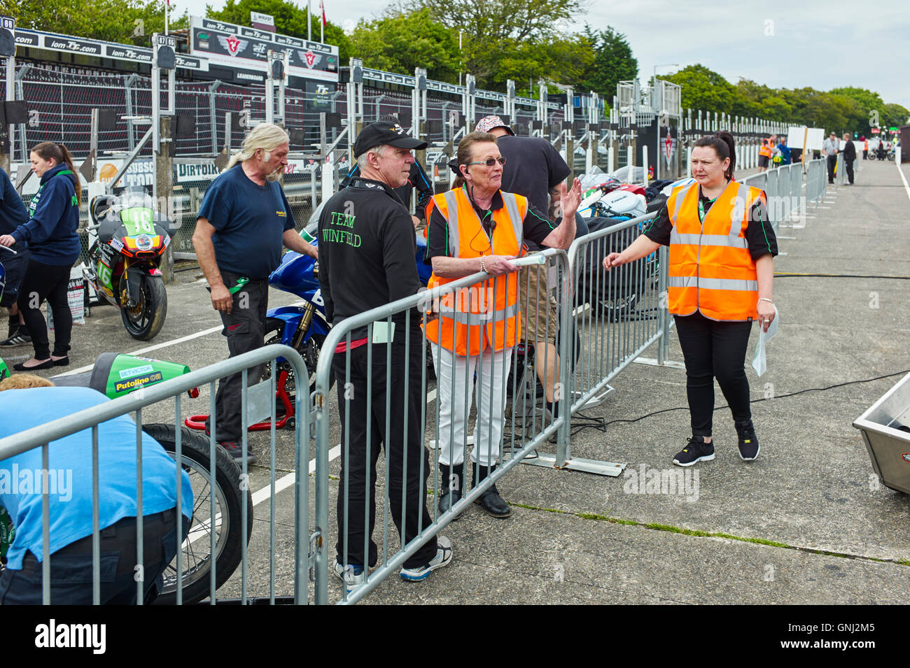 Officials positioning bikes before races at the Manx Festival of Motorcyling 2016 - Stock Image