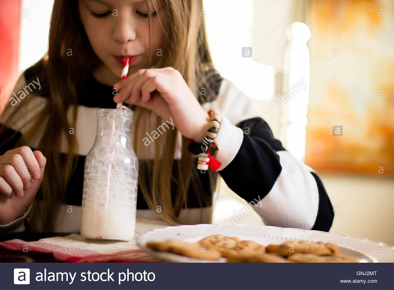Girl blowing bubbles in bottle of milk and plate of cookies - Stock Image