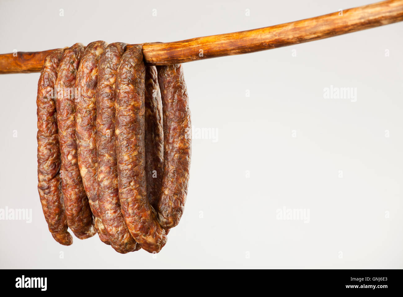 hanging smoked sausage on a stick on white background - Stock Image