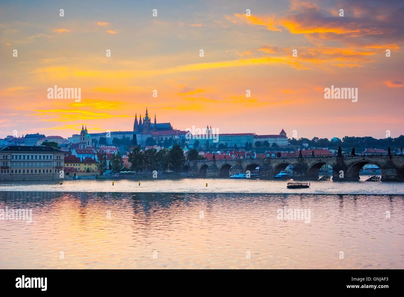 Sunset over Charles Bridge and Prague Castle from Smetanovo nabrezi along the River Vltava. Prague Czech Republic - Stock Image