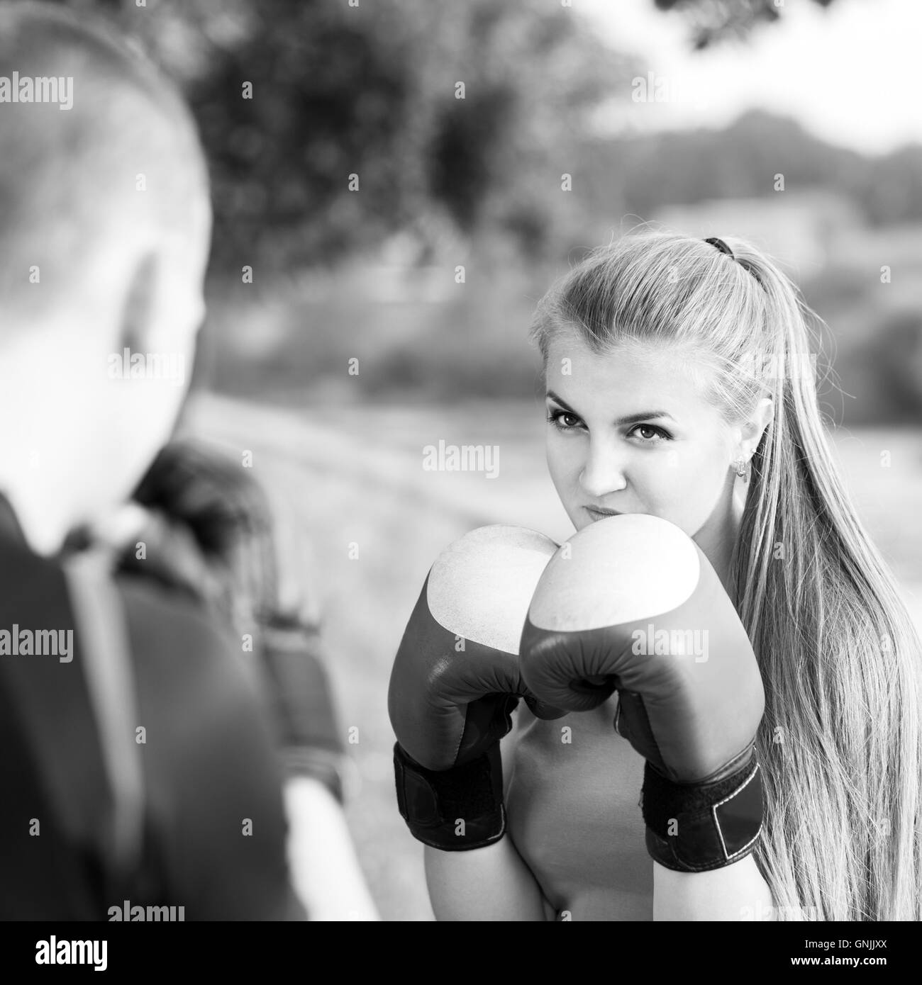 Young sporty woman training boxing with trainer at the park. Fitness outdoors workout black and white image - Stock Image