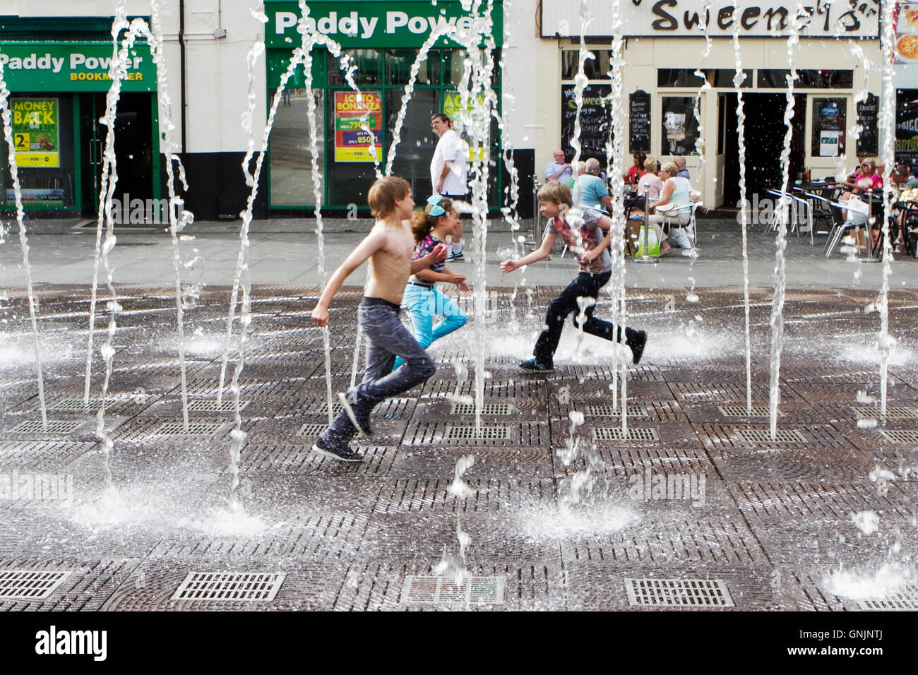 Children playing in the pulsating fountains and water jets in Williamson Square, Liverpool, Merseyside, UK Stock Photo