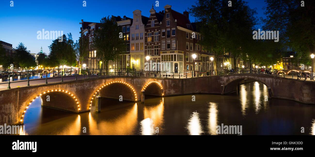 Illuminated bridges at Kaisersgracht and Leidsegracht, canal ring area, Jordaan district, Amsterdam - Stock Image