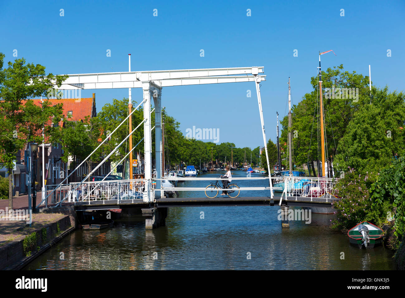 Woman cyclist cycling on bascule vertical-lift bridge, lift up drawbridge over canal waterway, Edam, The Netherlands - Stock Image