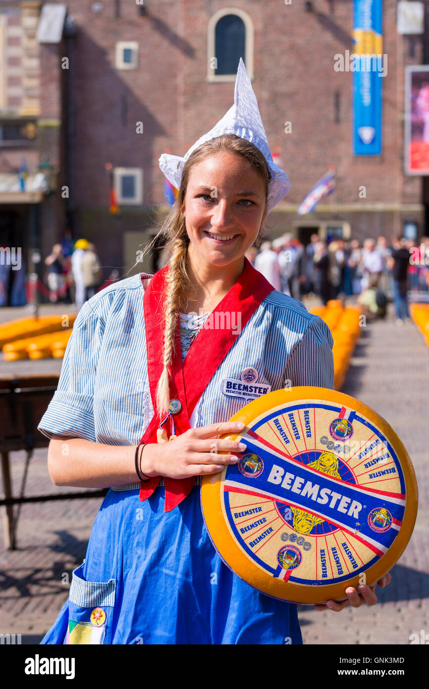 Dutch girl Kaasmeisje wearing traditional costume and Beemster Gouda cheese, Alkmaar cheese market, The Netherlands - Stock Image