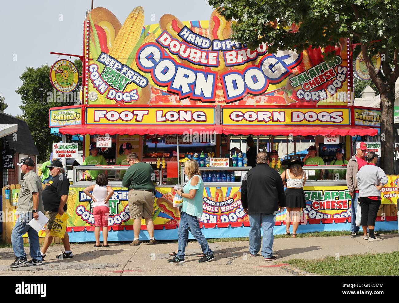 Fairgoers in front of a corn dog stand at the Minnesota State Fair. - Stock Image