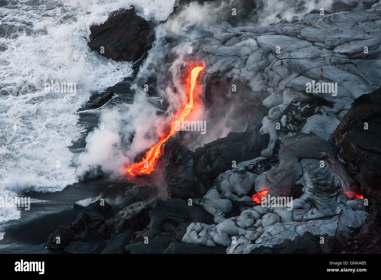 Lava comes out of lava tubes and meets ocean water on Big Island, Hawaii - Stock Image