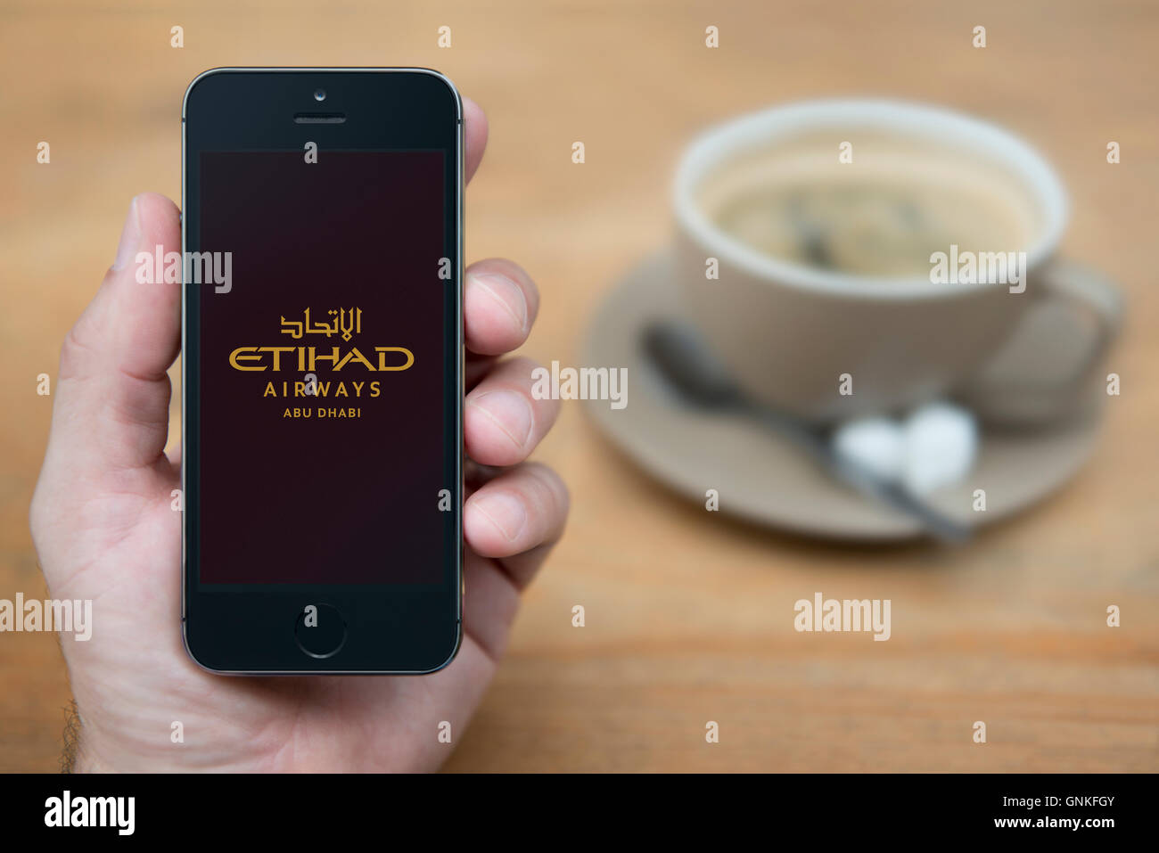 A man looks at his iPhone which displays the Etihad Airways logo, while sat with a cup of coffee (Editorial use - Stock Image