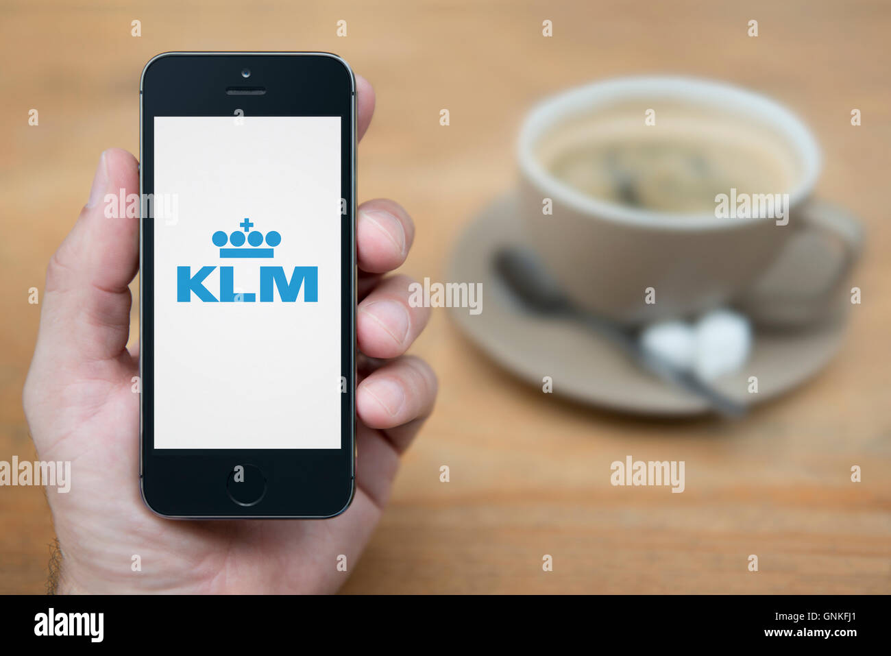 A man looks at his iPhone which displays the KLM logo, while sat with a cup of coffee (Editorial use only). - Stock Image