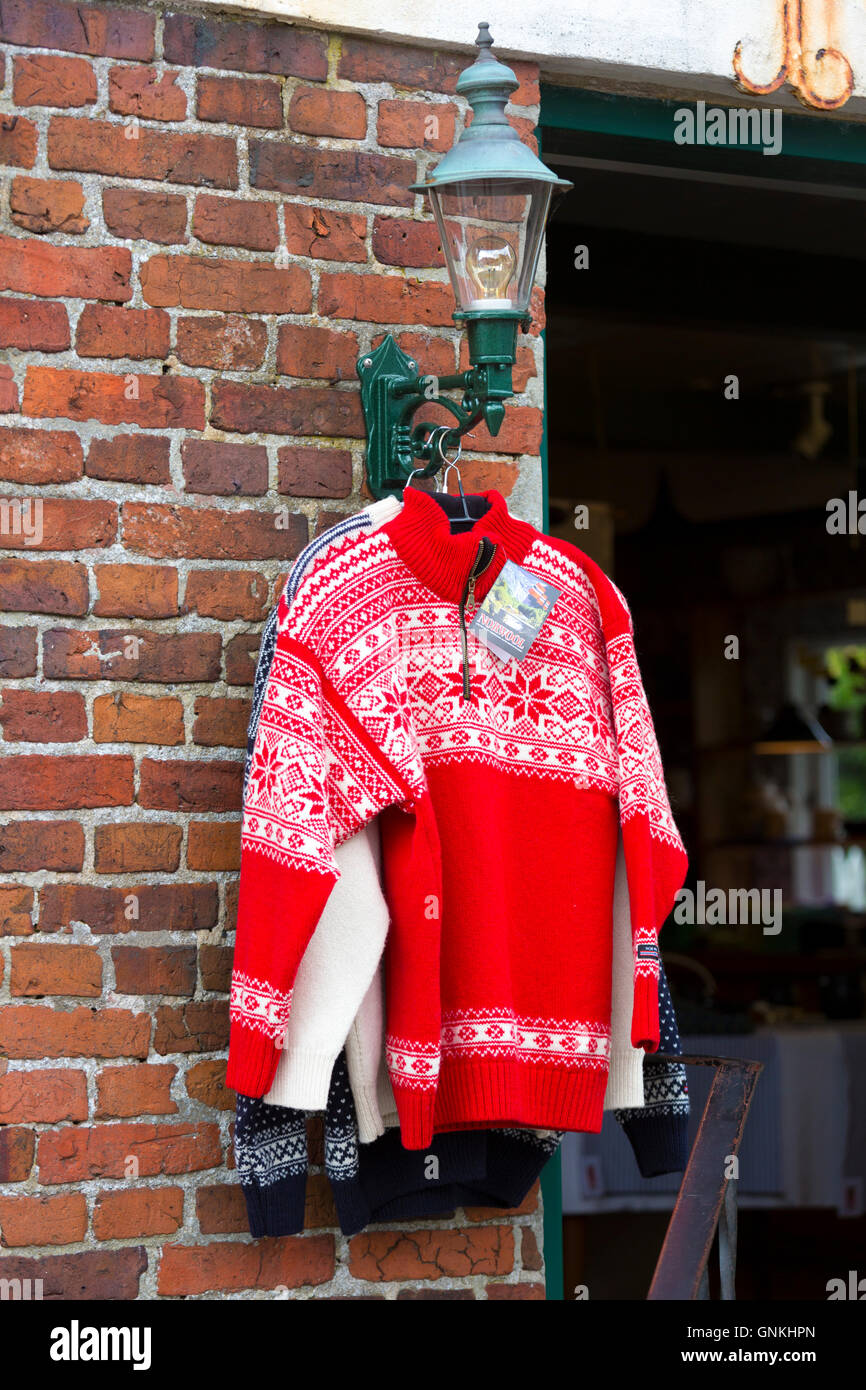 Red jumper, traditional Nordic wool sweaters on sale as gifts and souvenirs at shop in Fano in Denmark - Stock Image