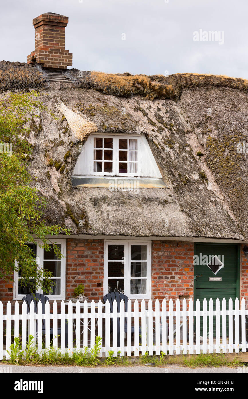 Traditional thatched cottage house with shabby thatch on Fano Island - Fanoe - South Jutland, Denmark - Stock Image