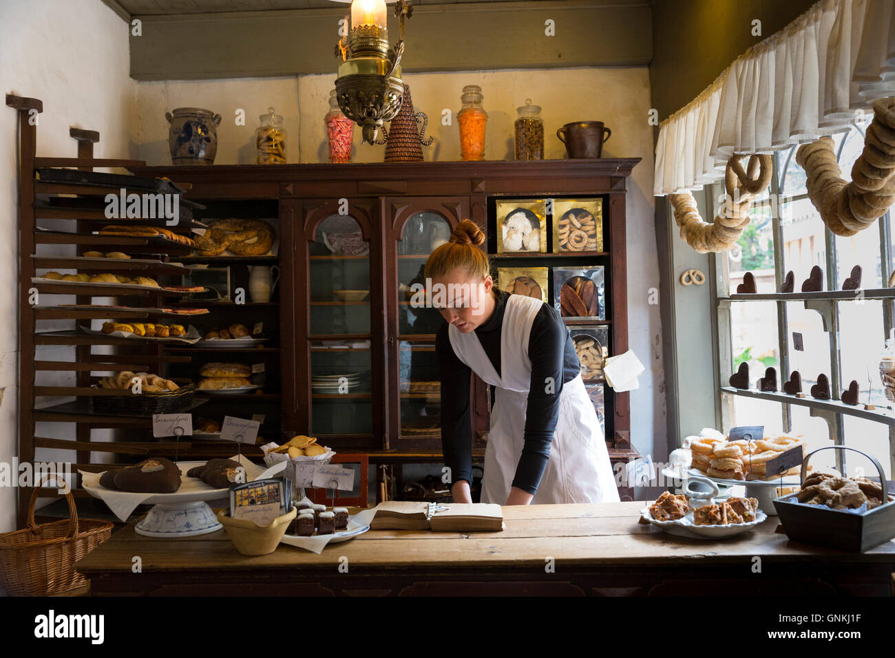 Costume character in period bakery at Den Gamle By, The Old Town, folk museum at Aarhus, Denmark - Stock Image