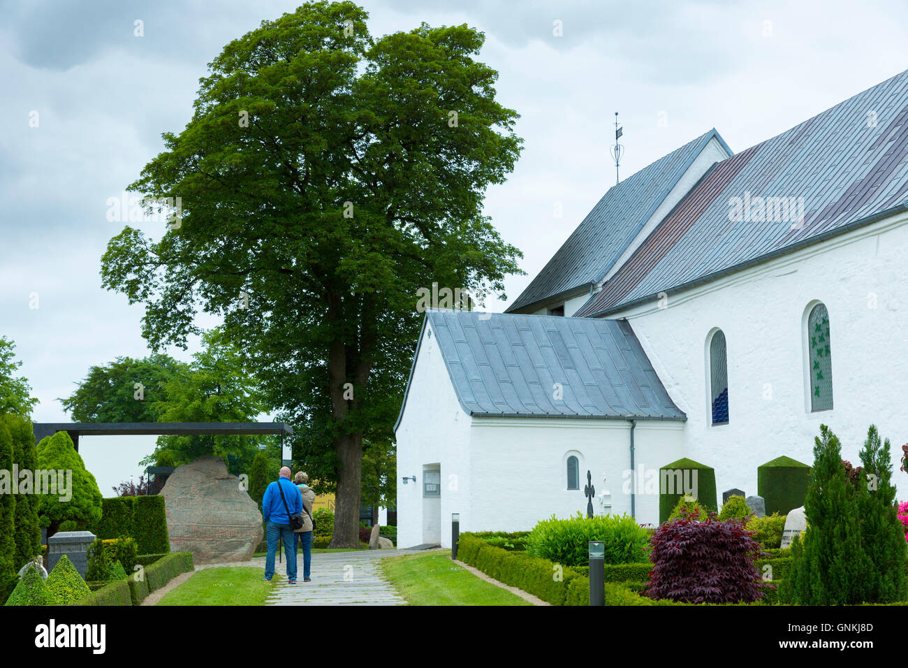 Visitors at Jelling Church and UNESCO Jelling Stones runestones, birthplace of Christianity in Denmark - Stock Image