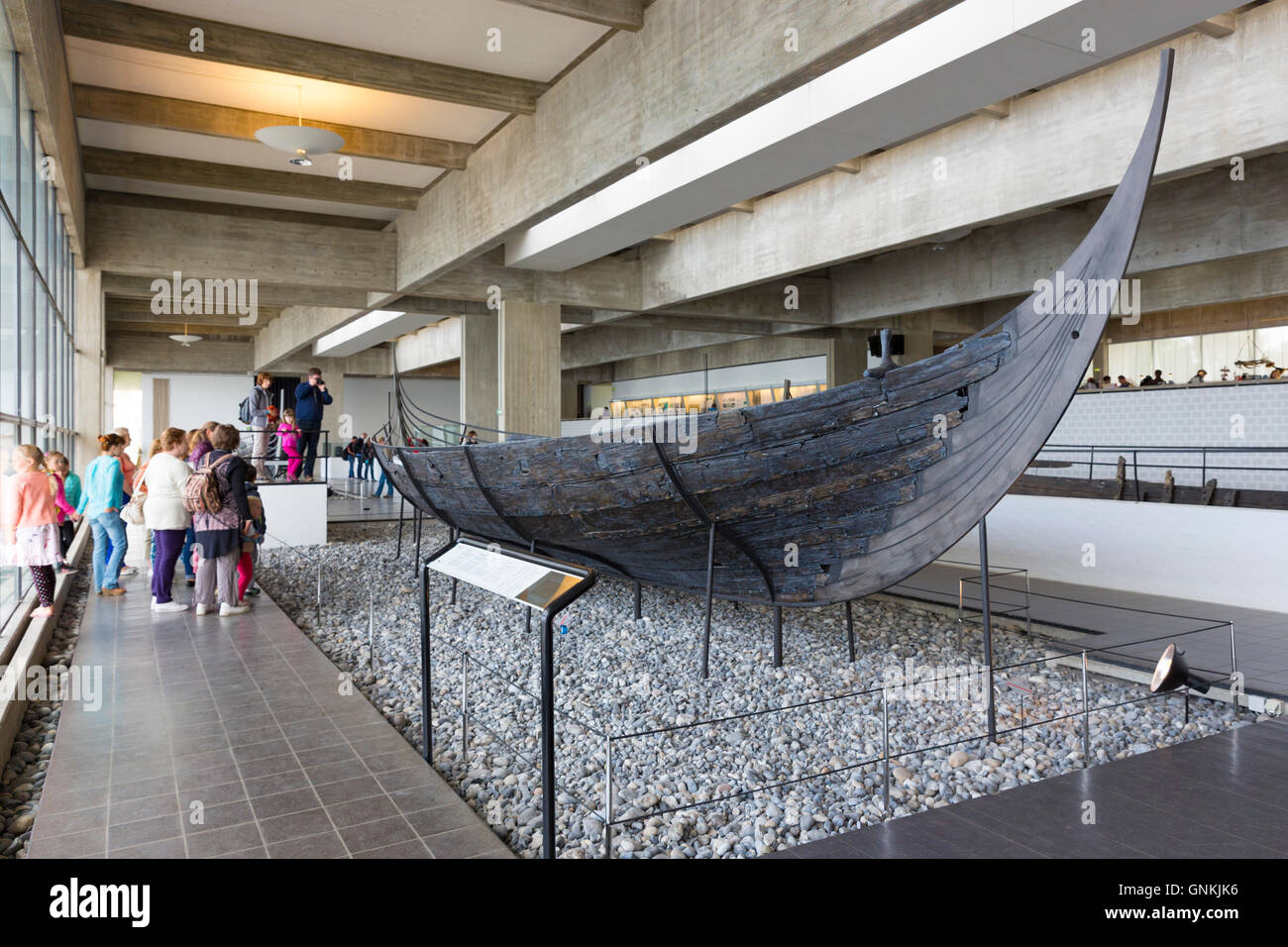 Tourists view Sculdelev original longboat exhibit at Roskilde Viking Ship Museum in Zealand, Denmark - Stock Image