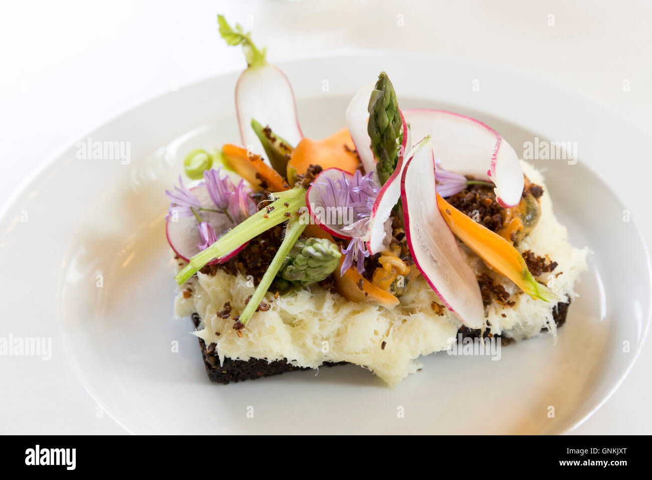 Lunch snacks cod fish Smorrebrod - smorgasbord Nordic open sandwich on minimalist white china plate - in Denmark - Stock Image