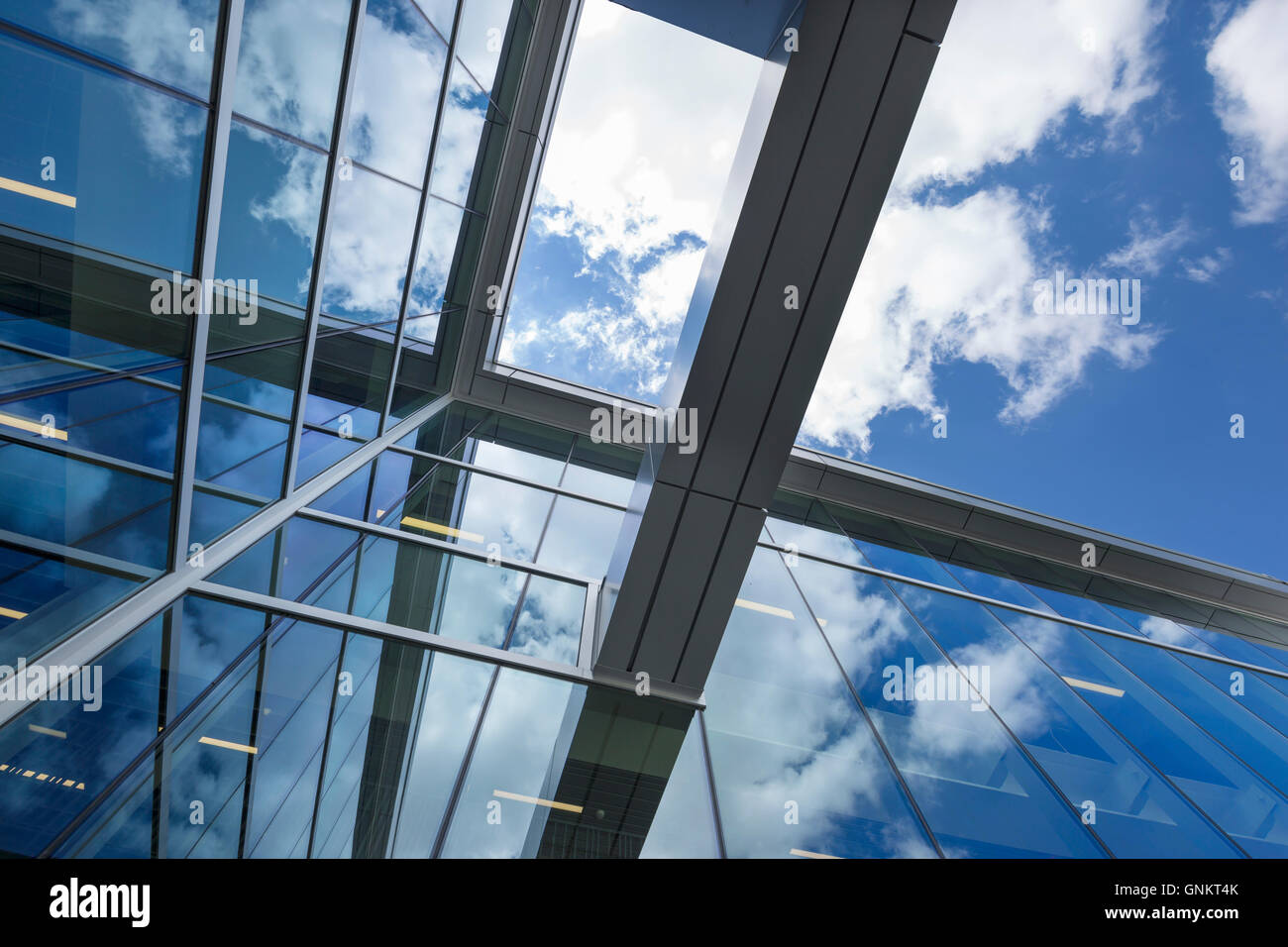 PUFFY WHITE CLOUDS BLUE SKY REFLECTED ON GLASS OFFICE BUILDING WINDOWS Stock Photo