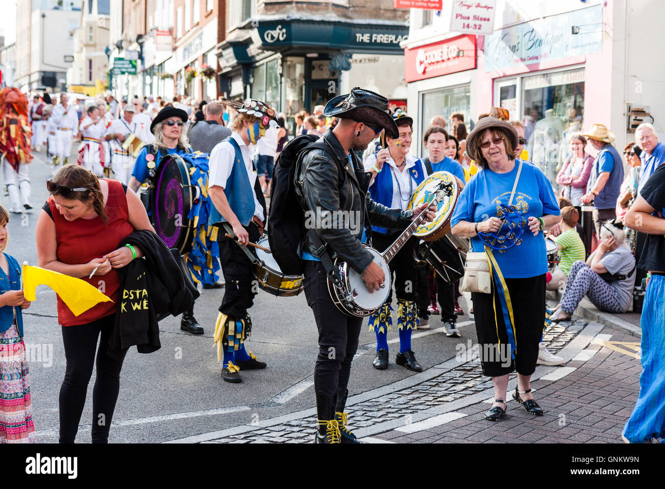 Broadstairs Folk Week. Parade. Royal Liberty Morris group, dancing in a town street, with their banjo player dressed - Stock Image