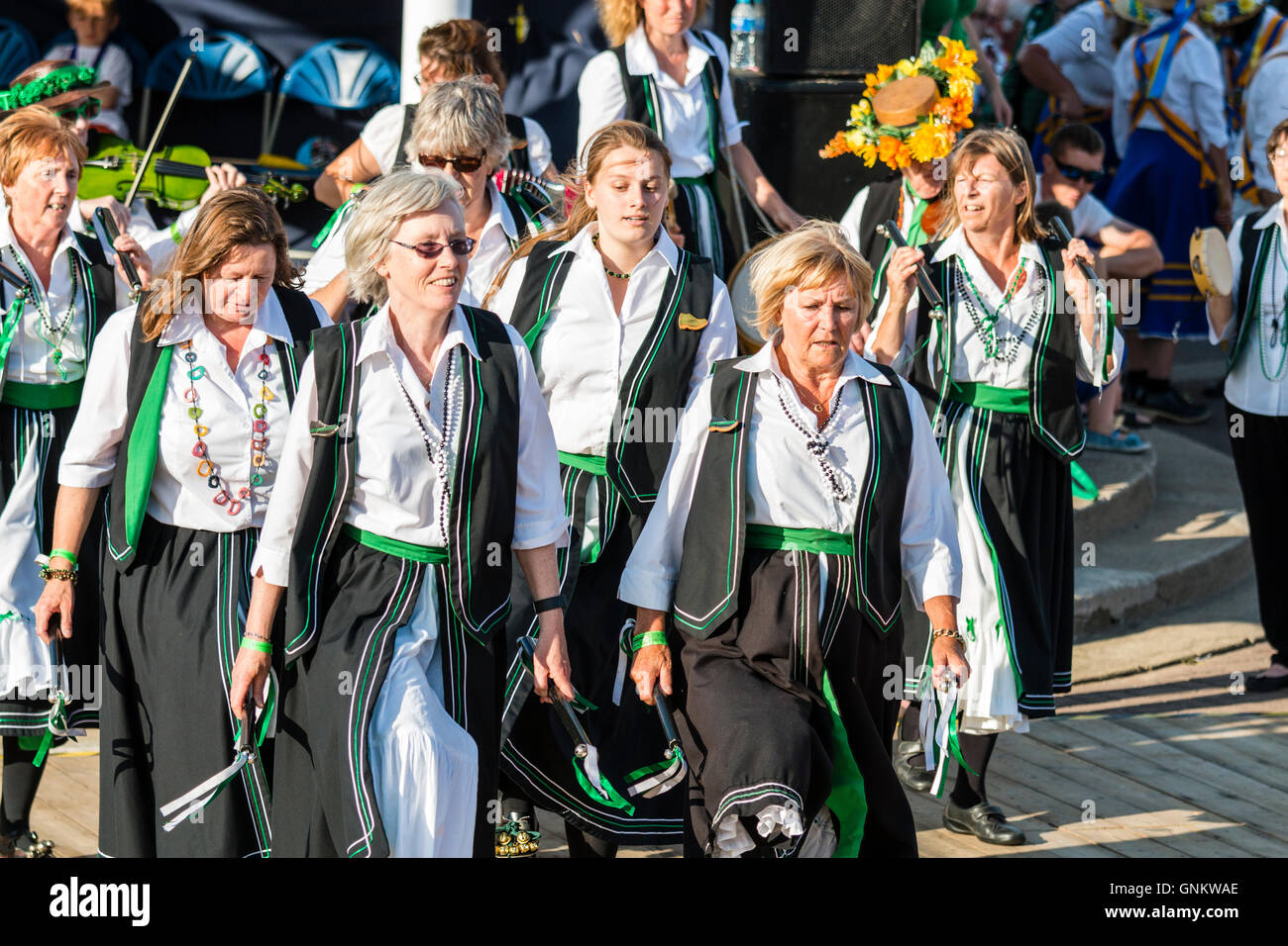 Broadstairs Folk Week Festival. Offcumduns Ladies Morris group in their green and black costumes, holding small - Stock Image
