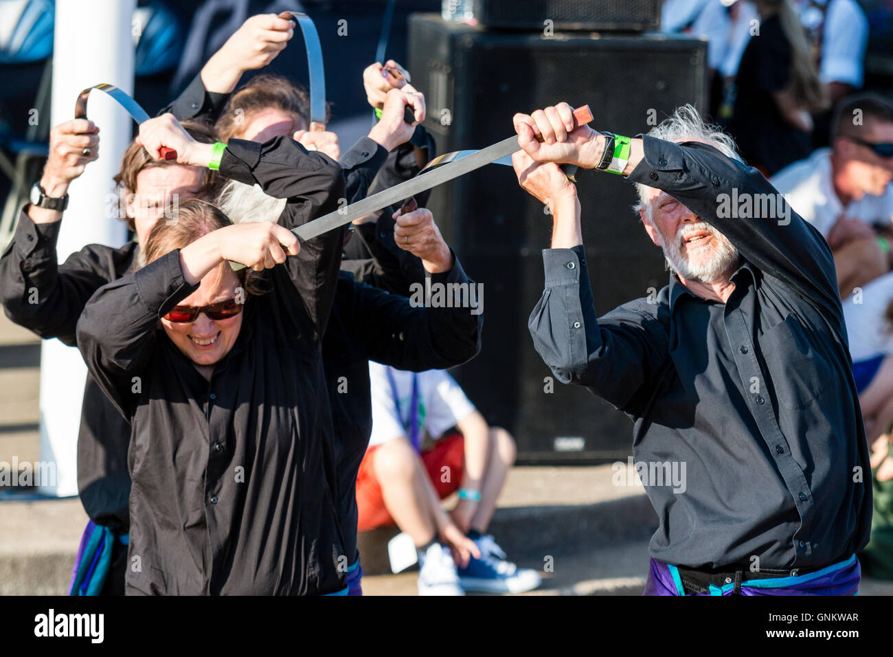 English Folk dancers, the Hawksword Rapper Morris men dancing with flat blade knifes on an outdoors wooden deck. - Stock Image
