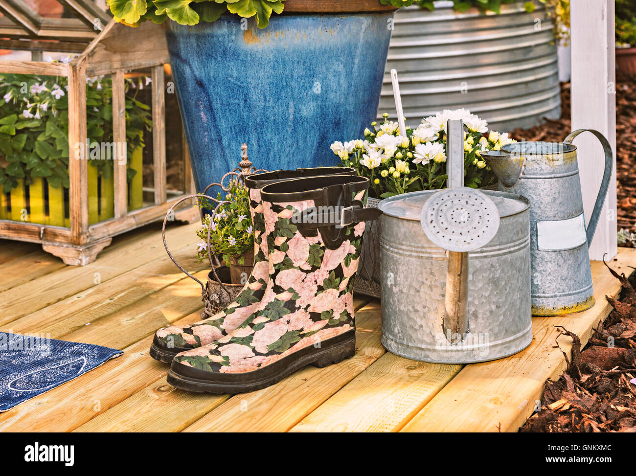 Image of rubber boot and watering cans on wooden terrace. Stock Photo