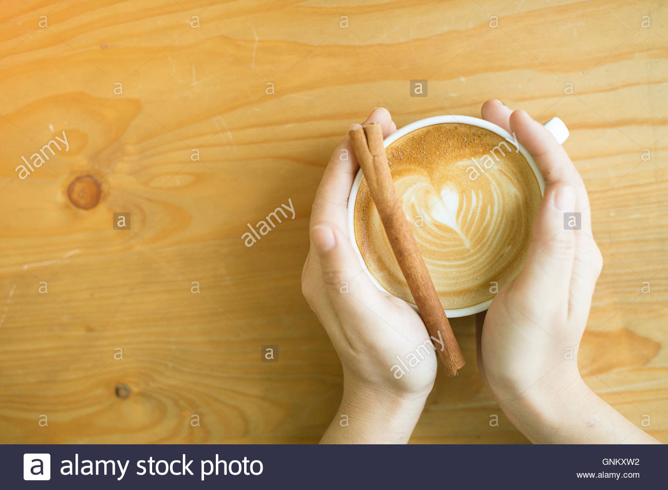 female hand  holding coffee cup in early morning on wooden table and soft flare filter and cross process warm tone - Stock Image