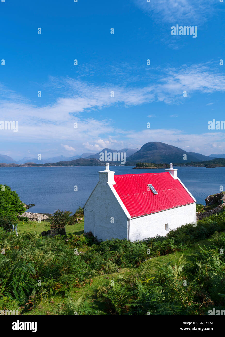 Small white cottage with red roof beside Loch Shieldaig in Torridon, on North Coast 500 tourist route, Highland, - Stock Image