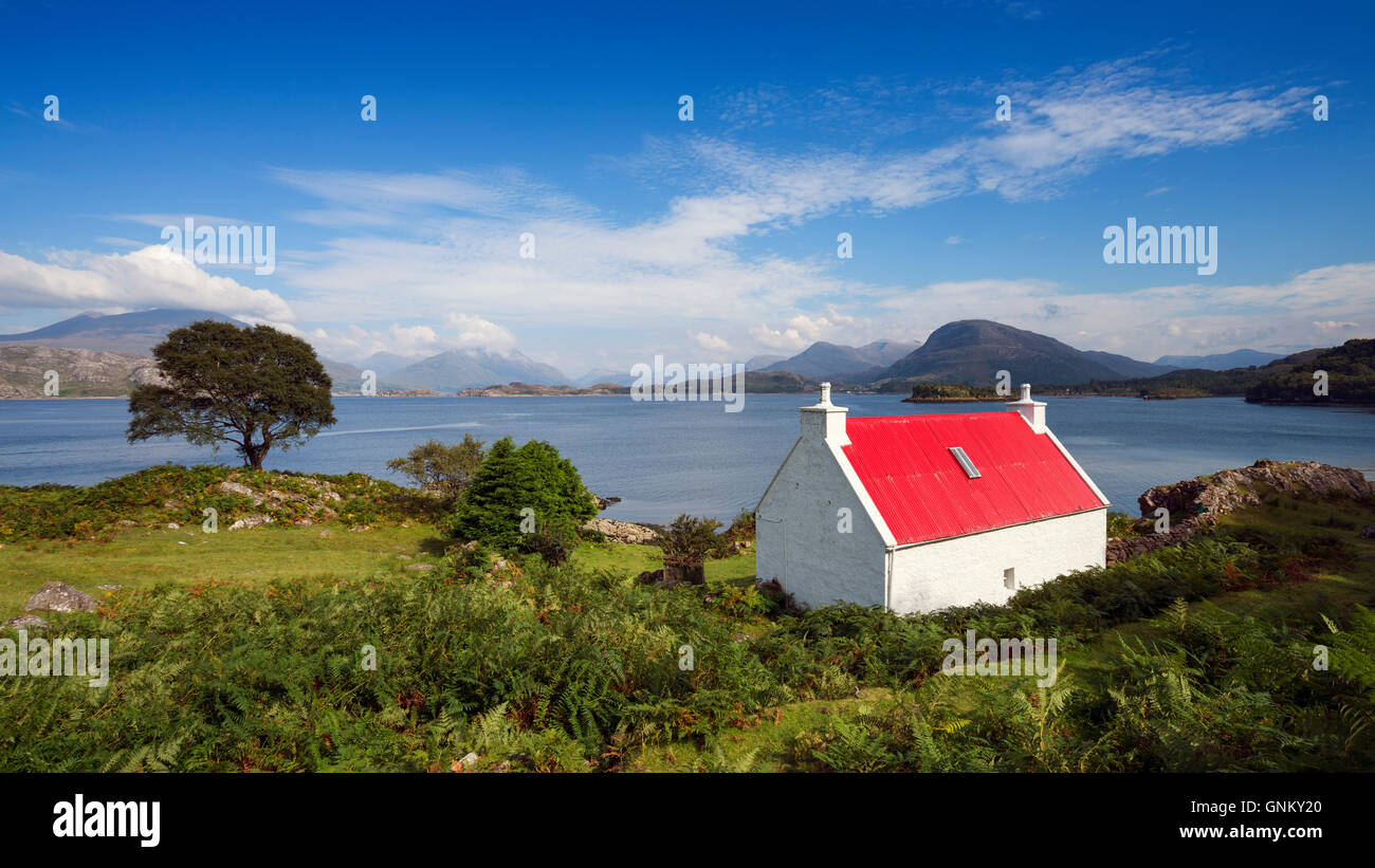 Small cottage with red roof beside Loch Shieldaig in Torridon, on North Coast 500 tourist route, Highland, Scotland, - Stock Image