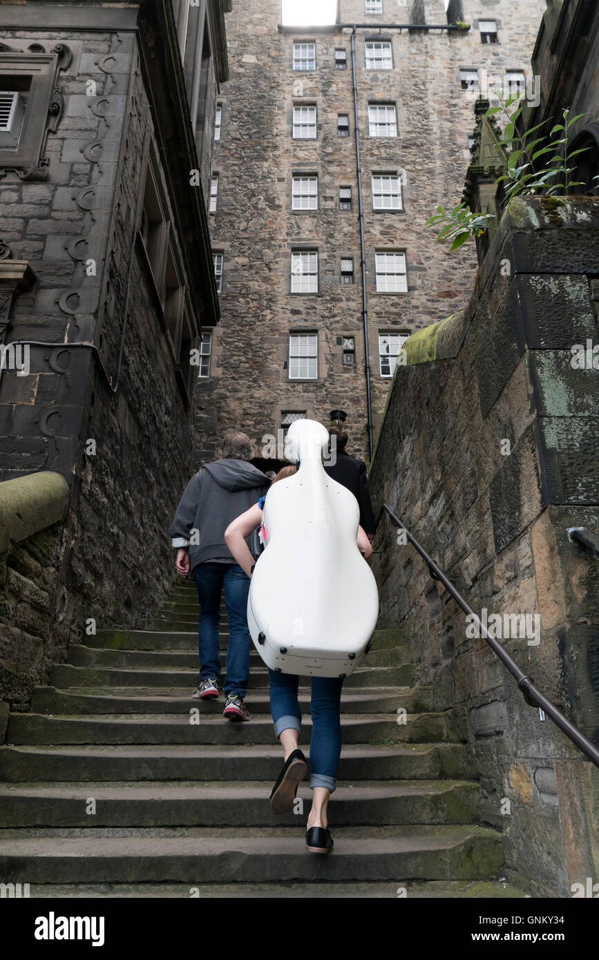Musician carrying cello up narrow lane during Edinburgh Festival 2016 in Scotland, United Kingdom - Stock Image