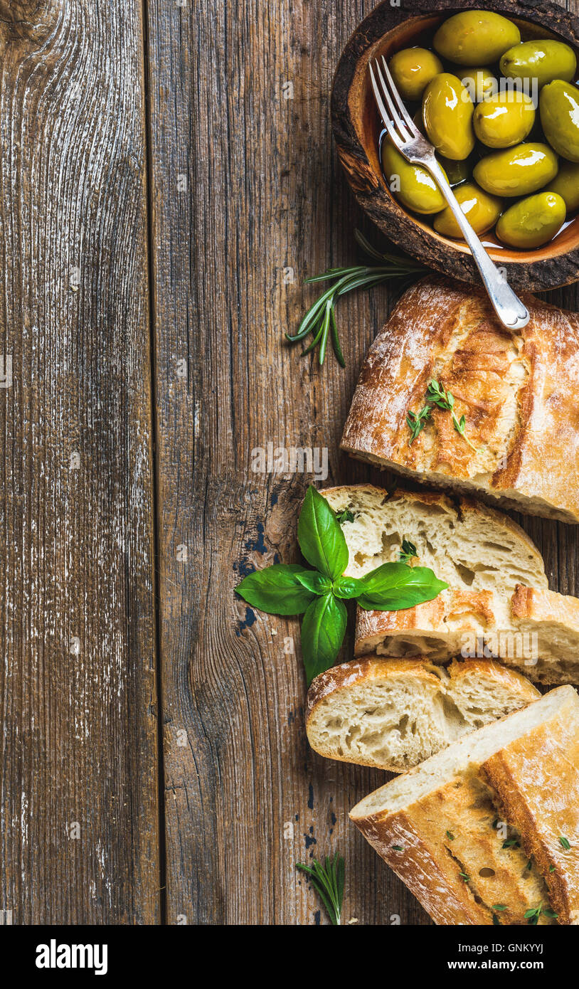 Green olives and slices of ciabatta over rustic wooden background - Stock Image