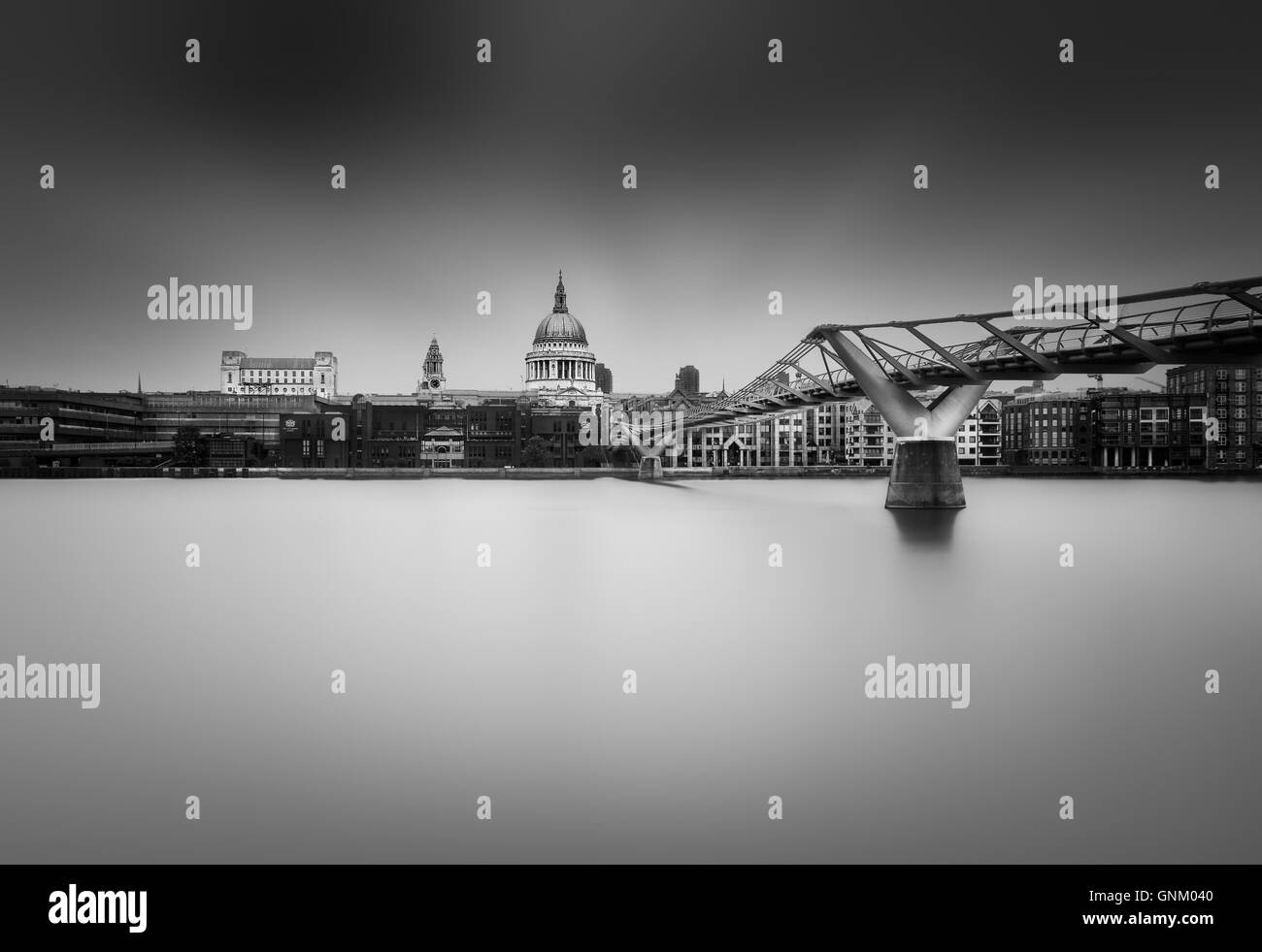 St. Paul's Cathedral, the Millenium Bridge and the Thames at high tide on a cloudy day. - Stock Image