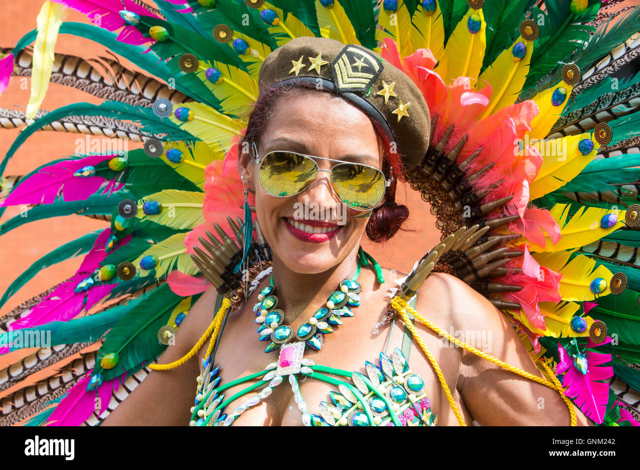 A festival performer in traditional costume parading at the Notting Hill carnival in West London - Stock Image
