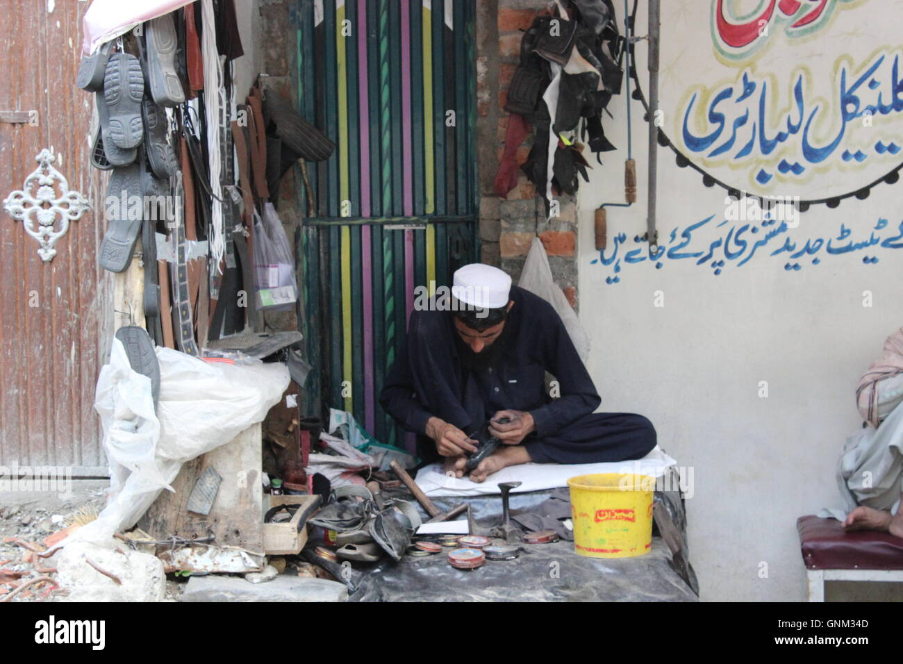 A picture of a shoe maker/ cobbler at work, he is mending shoes in his makeshift shop in a rural area. Stock Photo
