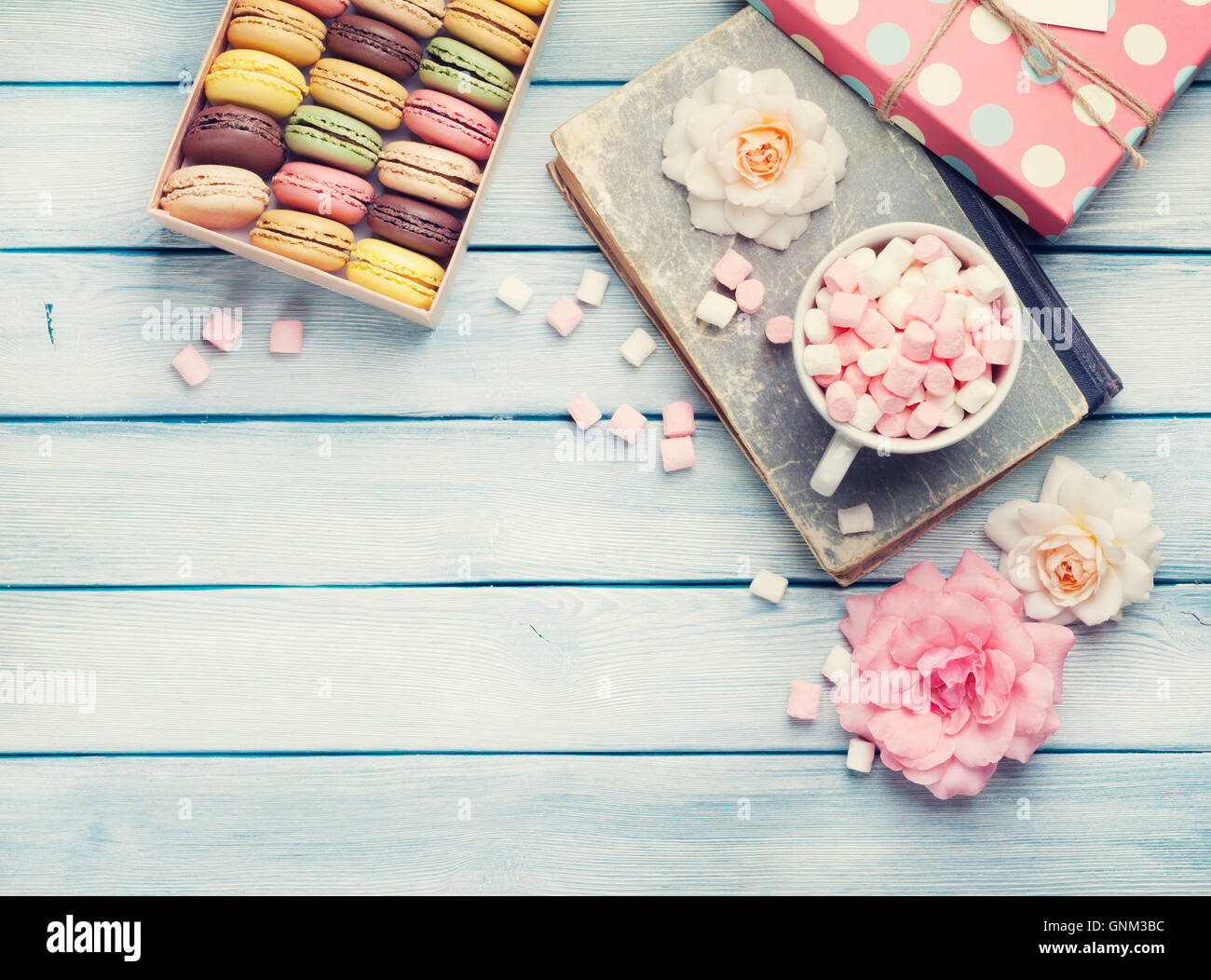 Colorful macaroons in a gift box and marshmallow in coffee cup on wooden table. Sweet macarons and flowers. Top - Stock Image
