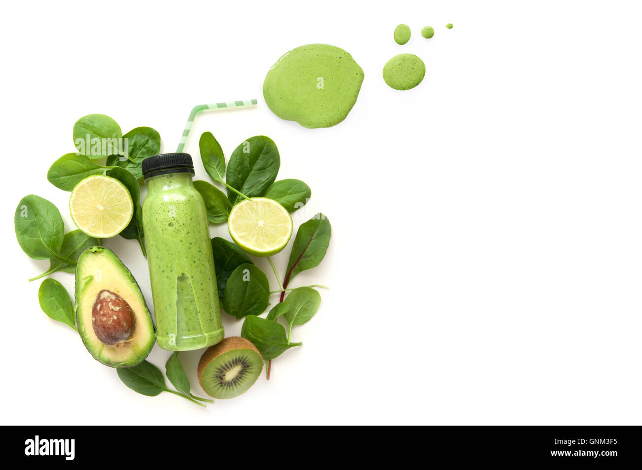 Bottled green smoothie surrounded by green foods including spinach and kiwi Stock Photo