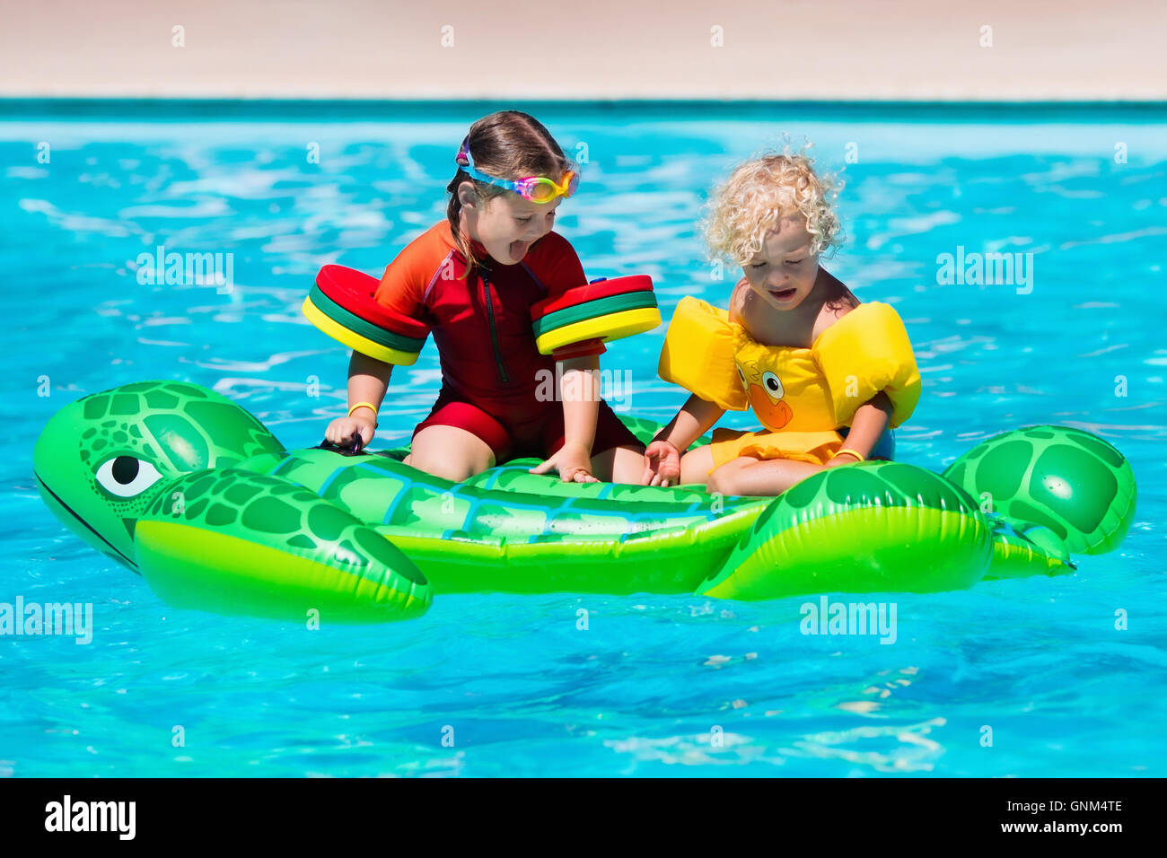 Happy little girl and boy playing in outdoor swimming pool ...