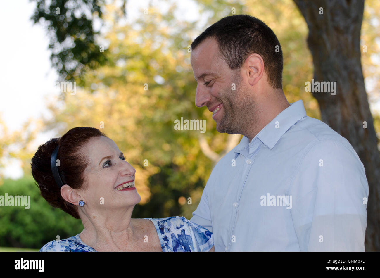 Mother and her adult son looking at each other outdoors on a fall evening cherishing the moments of life. - Stock Image