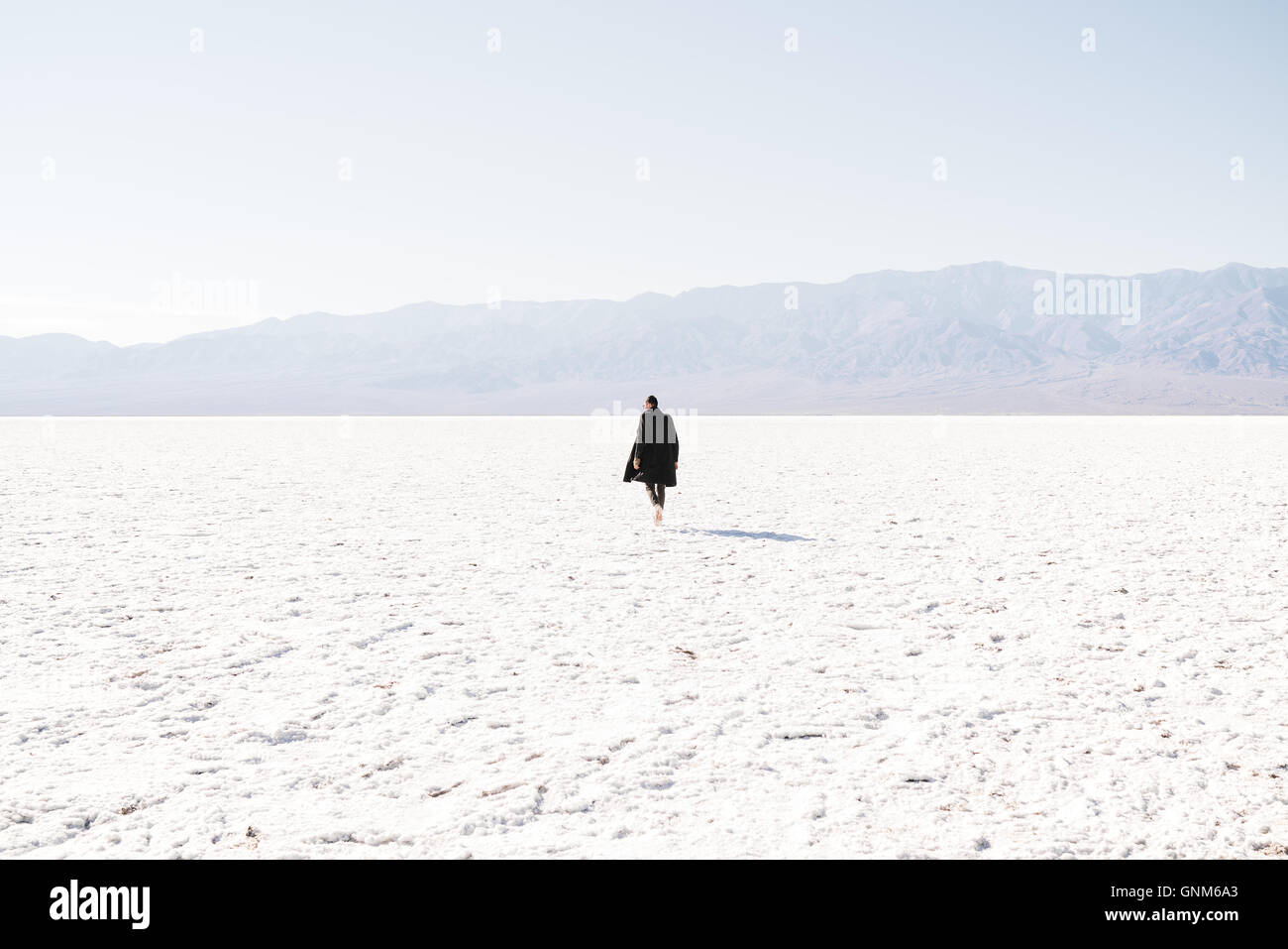 A man walks through the salt flats in Death Valley National Park - Stock Image